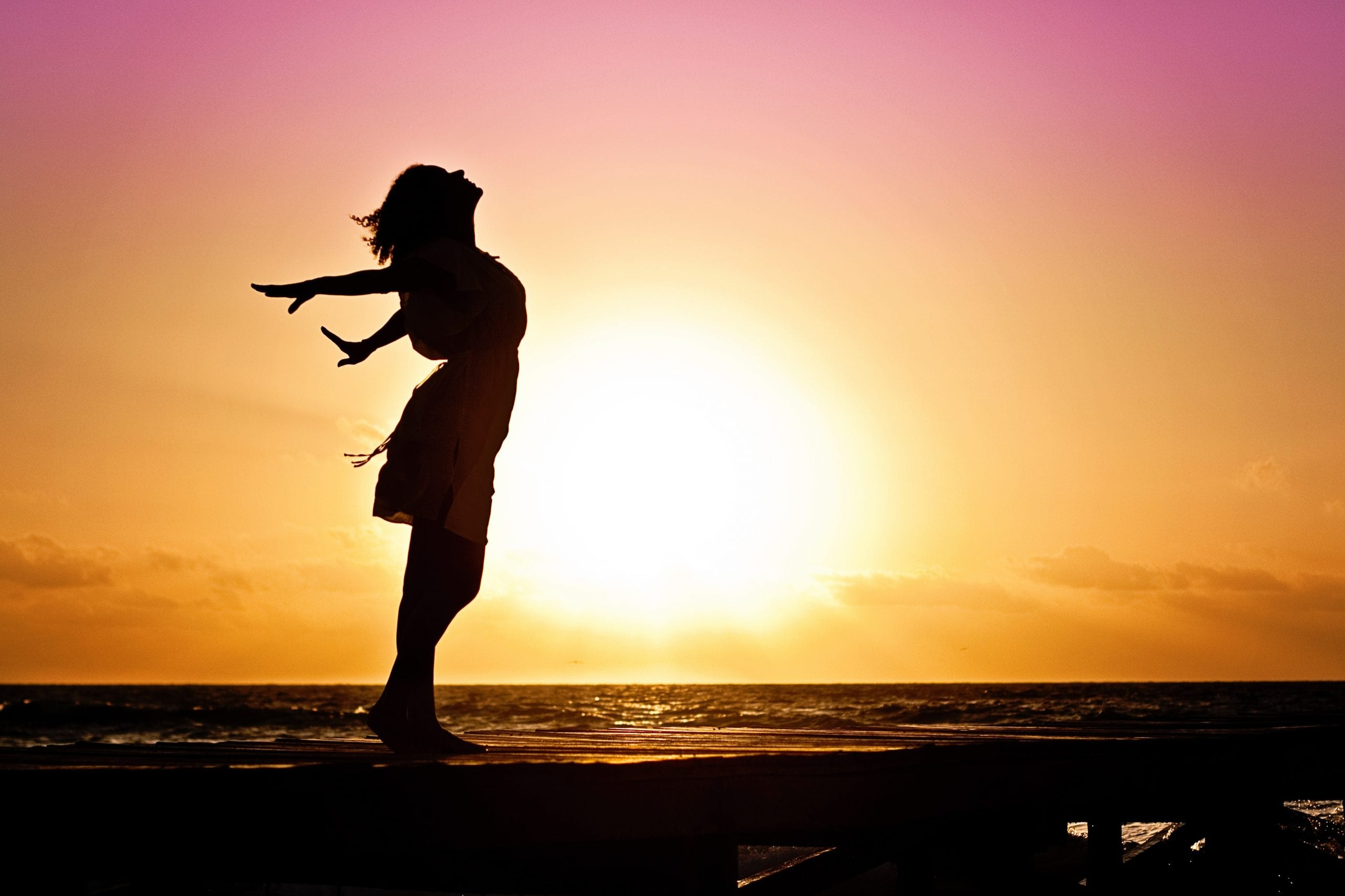 Silhouette of Woman with arms stretched - free and happy