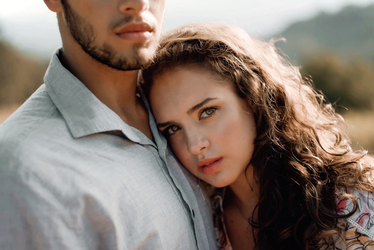 Sad looking woman resting on man's chest.